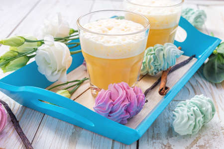 Traditional Homemade Eggnog with cinnamon and vanilla, marshmallow dessert and white eustoma flowers. Spring and easter concept Stock Photo