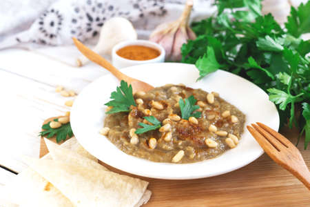 Baba ganoush - traditional arabian eggplant dip with parsley, paprika and flat bread on a wooden background Stock Photo