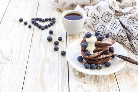 Hot coffee and buckwheat chocolate pancakes with blueberries and sour cream. Closeup. Breakfast and Love Concept