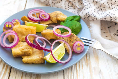 Crispy fried fish tilapia with lime and pickled onion. Selective focus. Closeup.