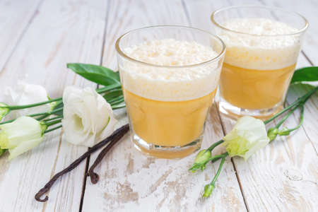 Traditional Homemade Eggnog with cinnamon and vanilla, and white eustoma flowers. Spring and easter concept