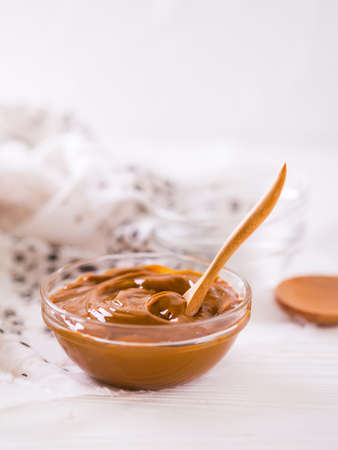 condensed: Bowl of homemade melted caramel sauce on wooden backgroung