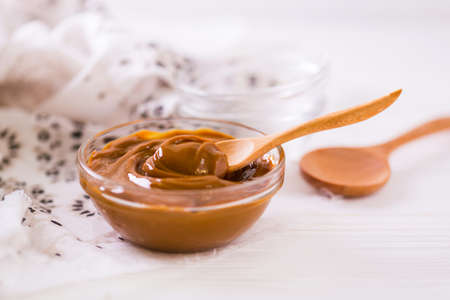 Bowl of homemade melted caramel sauce on wooden backgroung