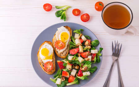 huevos de codorniz: Fresh salad with strawberry, spinach leaves, corn salad, walnuts and goat cheese.  Bruschettes with cherry tomatoes, fish pate and fried quail eggs. Healthy food concept Foto de archivo