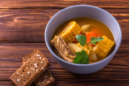 yam: Latin American food. Puchero soup with corn and parsley on wooden table. Traditional dish of Uruguay, Peru or Chile. Closeup