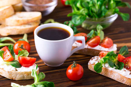 Bruschetta with ricotta, corn salad and cherry tomatoes on slices of toasted baguette or ciabatta. Cup of coffee. Traditional Italian appetizers. European cuisine. Selective focus