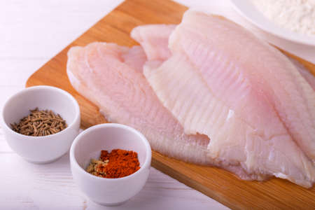 ingridients: Ingridients for cooking crispy fried fish tilapia. Raw fillet, fleur, cumin and spices. Healthy food concept