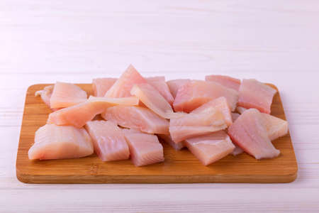ingridients: Ingridients for cooking crispy fried fish tilapia. Chopped raw fillet on cutting board. Healthy food concept Stock Photo