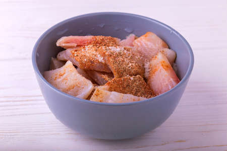 ingridients: Ingridients for cooking crispy fried fish tilapia. Chopped raw fillet in clay bowl with spices. Healthy food concept