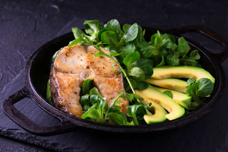 Grilled sheatfish fish steak with avocado, arugula and corn salad. Diet and healthy food. Selective focus, horizontal view Stock Photo