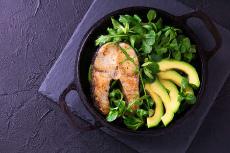 Grilled sheatfish fish steak with avocado, arugula and corn salad. Diet and healthy food. Selective focus, top view