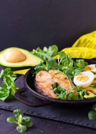 Grilled sheatfish fish steak with avocado, boiled egg, arugula and corn salad. Diet and healthy food. Selective focus, horizontal view