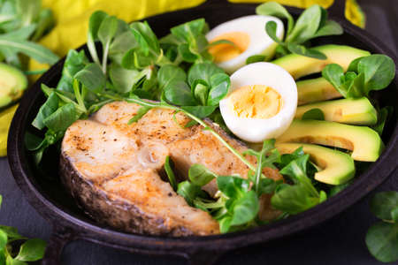 Grilled sheatfish fish steak with avocado, boiled egg, arugula and corn salad. Diet and healthy food. Selective focus, top view Stock Photo