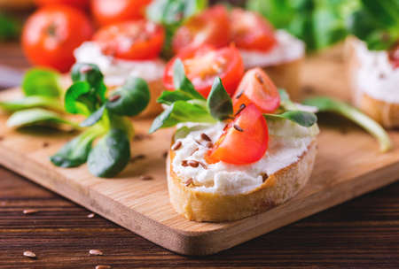 Bruschetta with ricotta, spinach, corn salad and cherry tomatoes on slices of toasted baguette or ciabatta. Traditional Italian appetizers. European cuisine. Selective focus