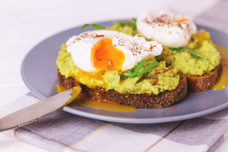 Rye bread toast with poached egg, puree avocado, spices and arugula. Continental breakfast. Healthy food concept. Selective focus Stock Photo