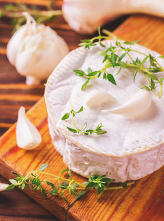 Traditional French homemade Camembert cheese with thyme and garlic. European cuisine. Selective focus. Stock Photo