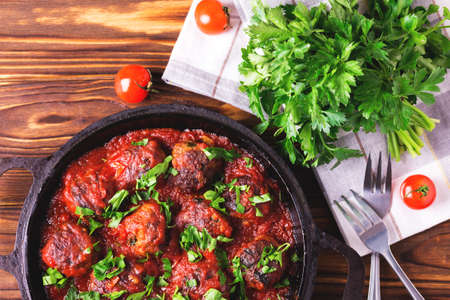 marinara sauce: Traditional Italian beef meatballs, tomato sauce and parsley.  Selective focus. Wooden background.