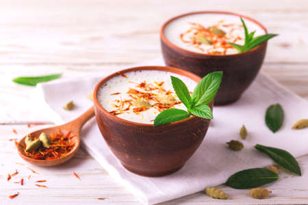 Traditioneller indischer Mandel-Lassi-Quark mit Kardamom, Minze und Safran serviert in Terrakotta-Gläsern. Kesariya. Keshariya. Kesar. Joghurt-Smoothie Standard-Bild