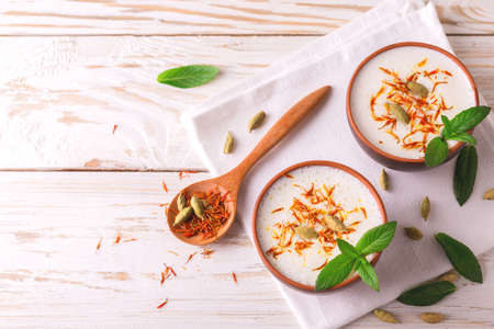Traditional Indian almond lassi curd with cardamon, mint and saffron served in terracotta glasses. Kesariya. Keshariya. Kesar. Yogurt smoothie Stock Photo