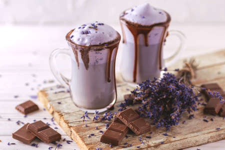 Coffee cup of cappuccino with homemade lavender and chocolate syrup and flowers on tray. Cosy breakfast. Stock Photo