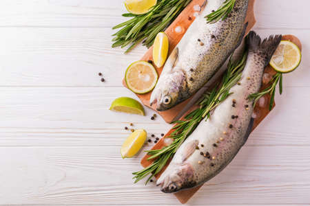 Seafood. Two raw rainbow trouts marinated with lime, peper, spices and rosemary on wooden board. Healthy food and dieting concept.