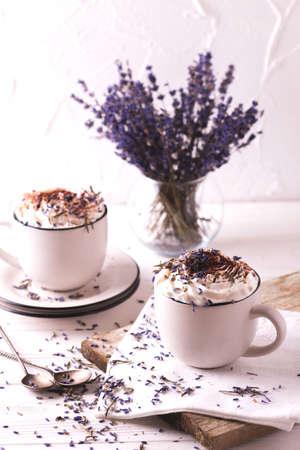 Zwei Schalen heiße Schokolade oder Kakao mit Schlagsahne, Lavendel und Schokolade auf weißem Holztisch Standard-Bild - 79744486