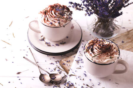 macchiato: Two cups of hot chocolate or cacao with whipped cream, lavender and chocolate on white wooden table