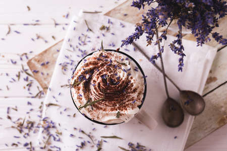 Two cups of hot chocolate or cacao with whipped cream, lavender and chocolate on white wooden table