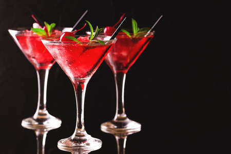 Strawberry daiquiri cocktail with lime, strawberry syrop, cherry and mint on black background. Summer drink, refreshment, Aperitif. Selective focus Imagens