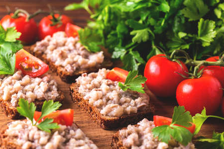 Bruschetta toast with kosher Forshmak paste, parsley and cherry tomatoes on slices of toasted baguette or ciabatta. Traditional Jewish and Swedish cuisine