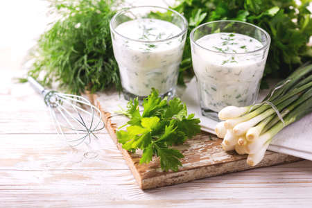 Ayran with fresh herbs - parsley, dill and green onion in glasses. Traditional Turkish yoghurt drink on wooden table.