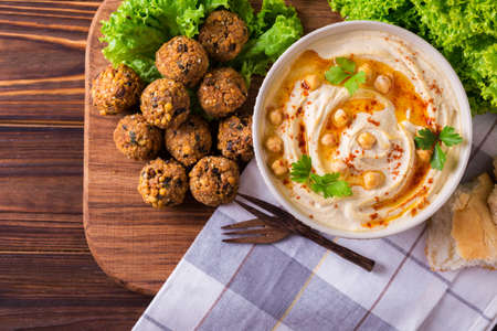 dipping: Traditional homemade hummus, falafel and chickpea served with salad and pita and spices on wooden table. Jewish Cuisine. Top view