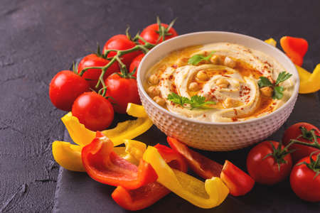 Traditionelle hausgemachte Hummus und Kichererbsen mit Gemüse und Gewürzen auf schwarzem Steintisch serviert. Jüdische Küche. horizontale Ansicht Standard-Bild - 80555888