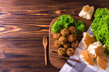 Traditional homemade falafel served with salad and pita on wooden table. Jewish Cuisine. Top view