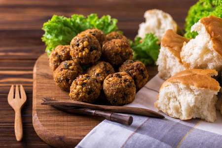 dipping: Traditional homemade falafel served with salad and pita on wooden table. Jewish Cuisine. Horizontal view