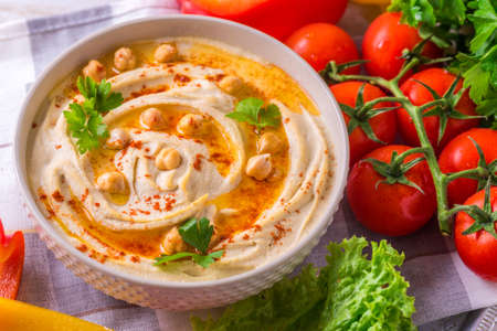 Traditional homemade hummus and chickpea served with vegetables and spices on wooden table. Jewish Cuisine. Top view Banque d'images