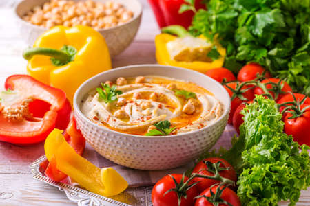 Traditional homemade hummus and chickpea served with vegetables and spices on wooden table. Jewish Cuisine. horizontal view