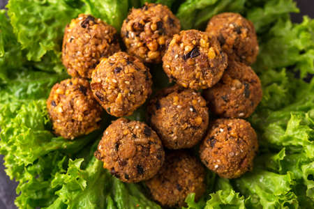 dipping: Traditional homemade falafel served with salad and pita on black stone table. Jewish Cuisine. Top view Stock Photo