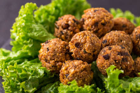 Traditional homemade falafel served with salad and pita on black stone table. Jewish Cuisine. Horizontal view Stock Photo