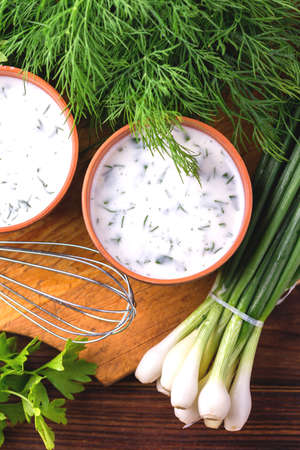 an onions: Ayran with fresh herbs - parsley, dill and green onion in clay bowls. Traditional Turkish yoghurt drink on wooden table.