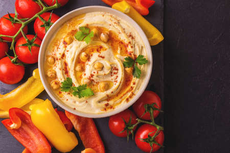 Traditional homemade hummus and chickpea served with vegetables and spices on black stone table. Jewish Cuisine. Top view