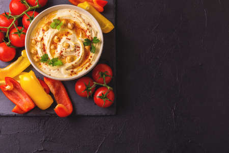 dipping: Traditional homemade hummus and chickpea served with vegetables and spices on black stone table. Jewish Cuisine. Top view