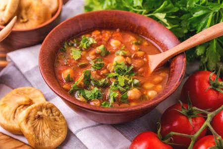 Tradicional magrebí, marroquí y argelino sopa de tomate Harira y los ingredientes. Servido con higos. Comida de Ramadán. Cocina judía tradicional Foto de archivo - 80558096
