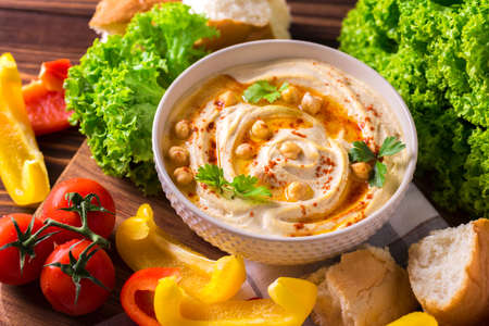 Traditional homemade hummus and chickpea served with vegetables and spices on wooden table. Jewish Cuisine. Top view Stock Photo