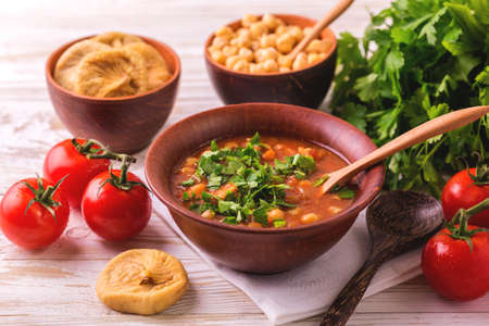 Traditional Maghreb, Moroccan and Algerian tomato soup Harira and ingredients. Served with figs. Ramadan food. Traditional Jewish cuisine 스톡 콘텐츠