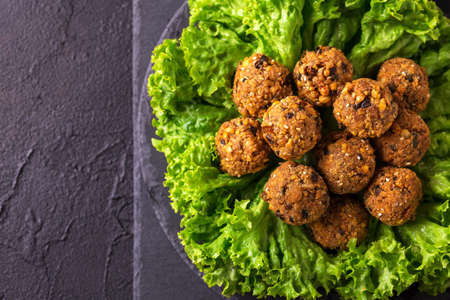 israeli: Traditional homemade falafel served with salad and pita on black stone table. Jewish Cuisine. Top view Stock Photo