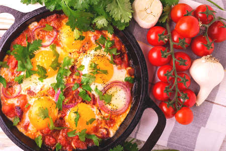 israeli: Shakshuka in iron pan with ingridients. Traditional Israeli cuisine. Fried eggs with vegetables. Top view. Middle eastern breakfast or lunch