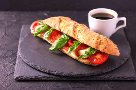 Ciabatta sandwich with caprese salad with espresso coffee on black stone table. Cherry tomatoes, green basil and mozzarella cheese. Italian food. Stock Photo