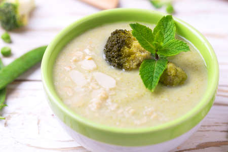 Broccoli and green peas puree soup decorated with mint leafes and almond flakes. Selective focus. Concept of healthy food. Vegetarian. Vegan. Horizontal view Stock Photo
