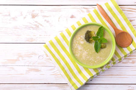 Broccoli and green peas puree soup decorated with mint leafes and almond flakes. Selective focus. Concept of healthy food. Vegetarian. Vegan. Top view. Copyspace Stock Photo